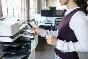 woman standing near printer sending something to print from her mobile phone