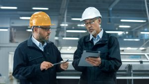 Two facility managers in hardhats discuss information on a tablet computer