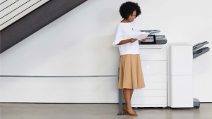 woman standing by a large printer