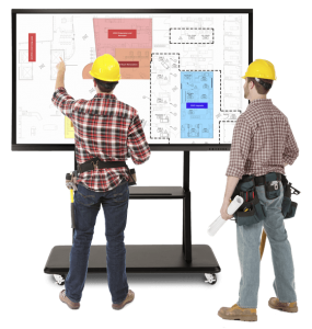 construction workers in hard hats using a gift smart screen to view construction plans